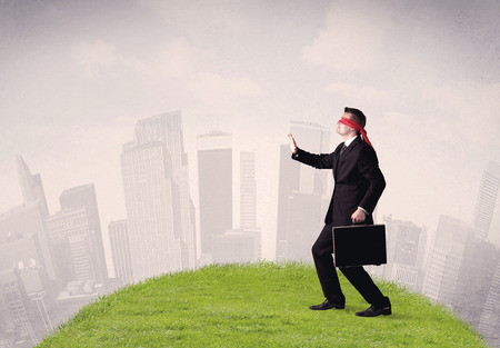 disoriented: Young blindfolded businessman steps on a a patch of grass with a cloudy city in the background