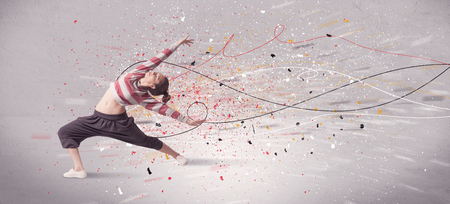 A young contemporary energetic dancer in action in front of a grey wall background with lines, spray dots and splatter concept Фото со стока