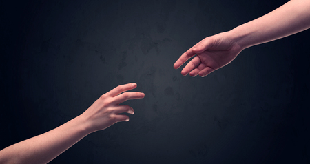 two generation family: Two male hands reaching out to one another, almost touching, in front of dark clear empty background wall concept