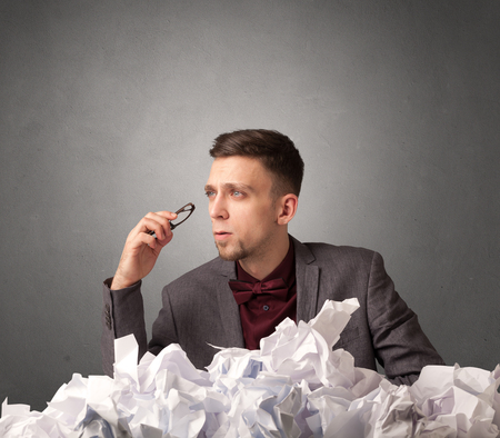 scrunch: Young businessman sitting behind crumpled paper with grey background Stock Photo