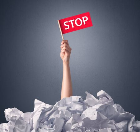 Female hand emerging from crumpled paper pile holding a red flag with stop written on it Stock Photo