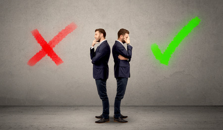 conflicted: Young conflicted businessman choosing between a right and a wrong direction