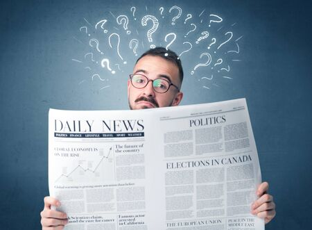 daily newspaper: Young confused businessman reading daily newspaper with question marks above his head