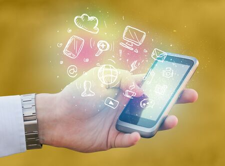 Hand holding smartphone with glowing multimedia icons Stock Photo