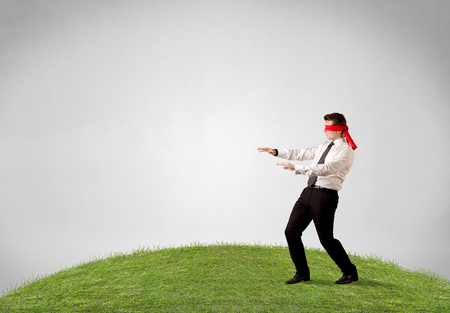 ojos vendados: Young blindfolded businessman steps on a patch of grass Foto de archivo