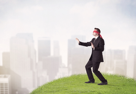 ojos vendados: Young blindfolded businessman steps on a a patch of grass with a city in the background