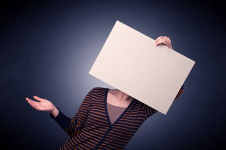 Young casual woman hiding behind a blank piece of paper Stock Photo
