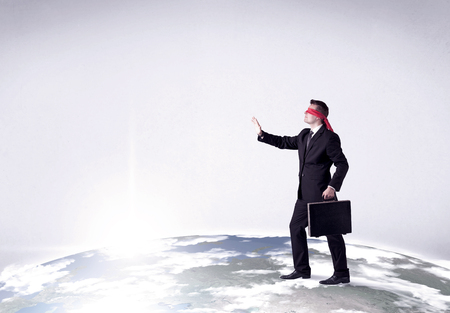 disoriented: Young blindfolded businessman steps on a realistic globe