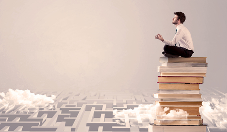 diligent: A serious businessman in suit sitting on a pile of giant books in front of a grey wall with clouds, labirynth Stock Photo