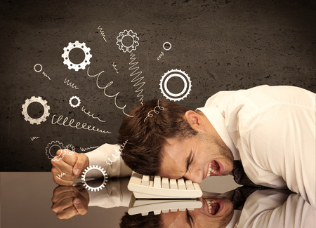 Falling apart illustration concept with cranks, cog wheels springing from a fed up and tired businessmans head resting on laptop keyboard Stock Photo