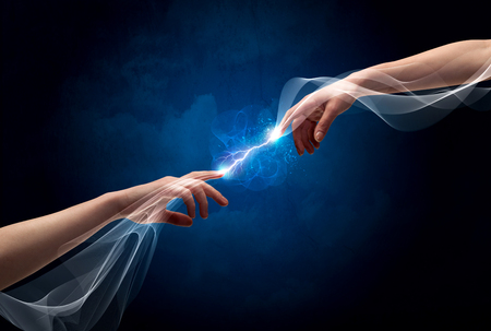 Two male arms reaching for each other, with a smoking electric current connecting their fingers in empty space background concept Stock Photo