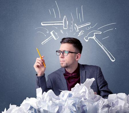 scrunch: Young businessman sitting behind crumpled paper with drawn hammers hitting his head