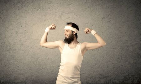 A young man with beard, headstrap and glasses posing in front of blank grey wall background, imagining he has big muscles