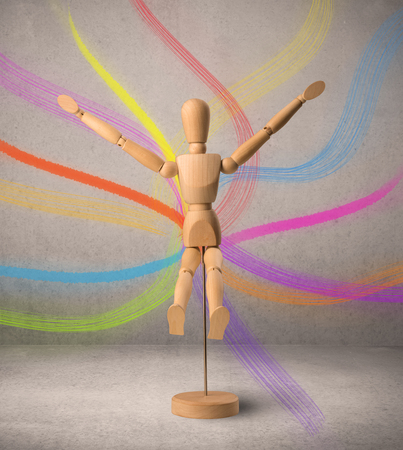 artists dummy: Wooden mannequin posed in front of a greyish background with colorful lines behind it