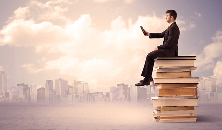 diligent: A serious student with laptop tablet in elegant suit sitting on a stack of books in front of cityscape with clouds