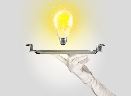 #74418296 - Serving a bright business idea concept using a bulb with bright sparkling warm yellow light presented on a silver plate & Serving A Bright Business Idea Concept Using A Bulb With Bright ...