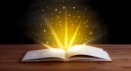 generosity: Yellow lights and sparkles coming from an open book