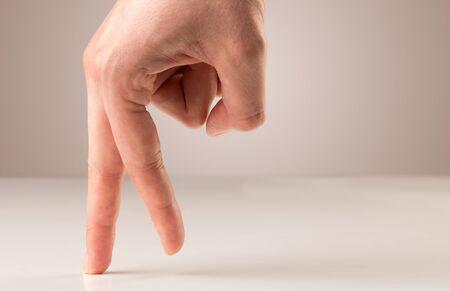 Female fingers walking on white surface