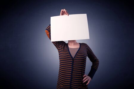 blankness: Young casual woman hiding behind a blank piece of paper Stock Photo