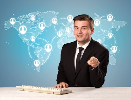 reason: Young handsome businessman sitting at a desk with a blue world map behind him Stock Photo