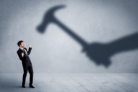 employe: Business person afraid of a shadow hand holding hammer concept on background Stock Photo