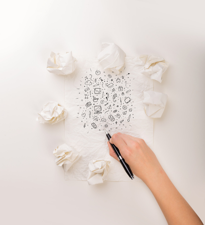 Female hand next to a few crumpled paper balls drawing mixed media icons Stock Photo