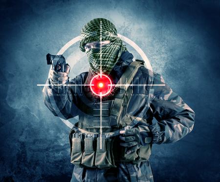 Gemaskerde terroristenmens met kanon en laserdoel op zijn lichaamsconcept