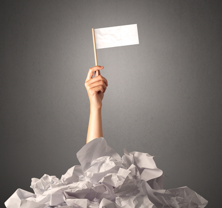 defeated: Female hand emerging from crumpled paper pile holding a white blank flag Stock Photo