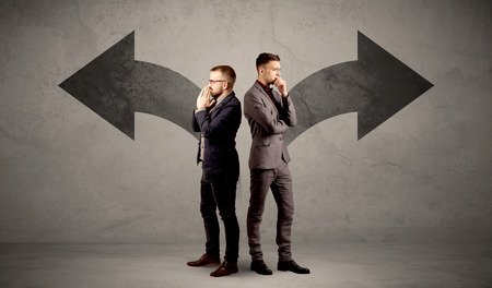 indecision: Young conflicted businessman choosing between two directions represented by black arrows