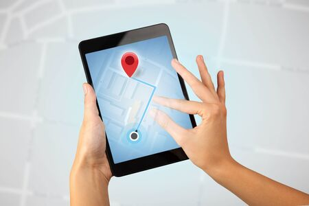 Female fingers touching tablet with map Stock Photo