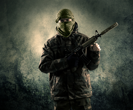 Portrait of a heavily armed masked soldier with grungy background concept Imagens - 75173509