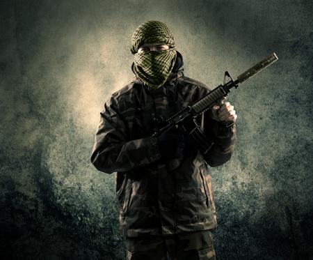 Portret van een zwaar bewapend gemaskerde soldaat met grungy achtergrond, concept