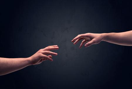ほとんど触れて、暗く澄んだ空の背景の壁の概念の前に、手を差し伸べる男性の 2 つの手