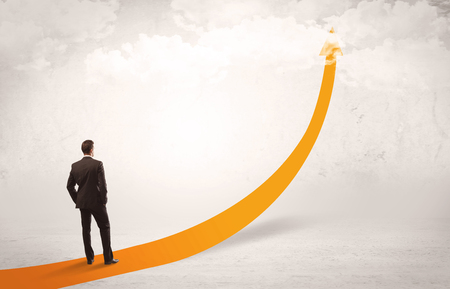A young adult salesman standing on a big orange arrow pointing up in a bright empty space concept Stock Photo