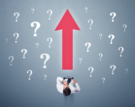 Young contemplating businessman stands in front of a big red arrow and white question marks