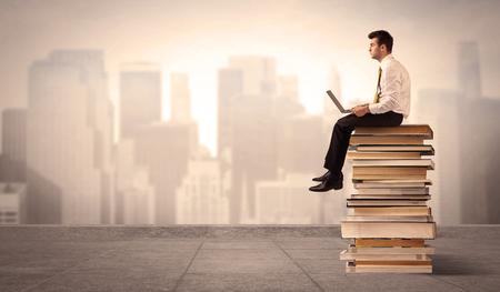 diligente: Un hombre de negocios serio con la tableta portátil en elegante traje sentado en una pila de libros delante del paisaje urbano