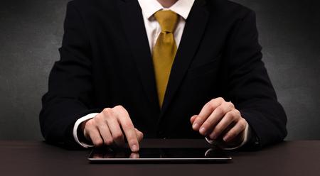 Businessman typing with dark background.