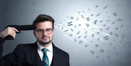 enough: Man shoots his head with gun and letters are coming out from his head. Stock Photo