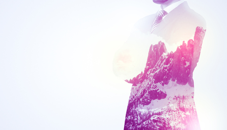 Businessman with sunny snowy mountain background.