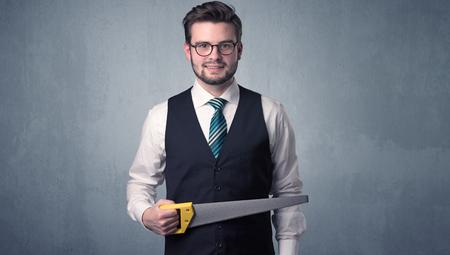 architect tools: Businessman holding tool with grey grunge background. Stock Photo