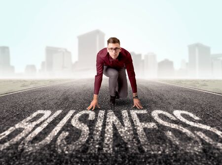 determined: Young determined businessman kneeling before business text