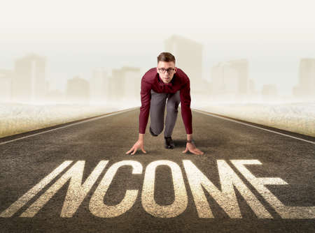 before: Young determined businessman kneeling before income sign Stock Photo