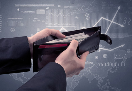 bribery: Businessmans hand takes out dollar from wallet with finance graphic on the background