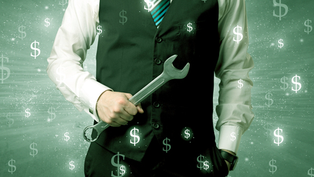 architect tools: Handsome businessman holding tool with dollar symbols around and with green background Stock Photo