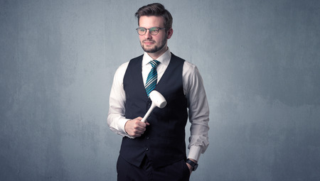 architect tools: Young, handsome, cute businessman holding tool with grey background