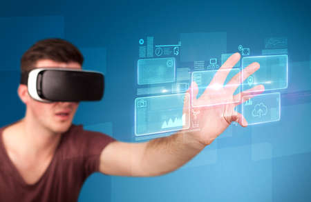 eyewear: Young impressed man wearing virtual reality goggles with blue squares containing data at his fingers Stock Photo