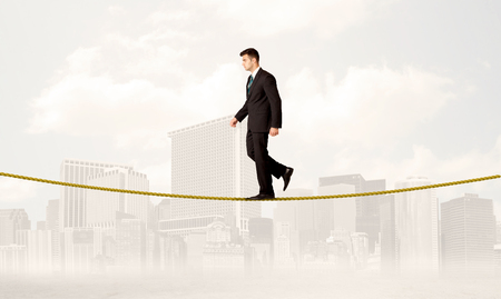 A young elegant businessman walking on tight golden rope in front of city buildings landscape background concept Stock Photo