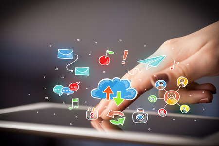 data synchronization: Female hands touching tablet with colorful social media icons Stock Photo