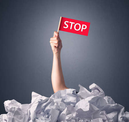 hand holding paper: Female hand emerging from crumpled paper pile holding a red flag with stop written on it Stock Photo