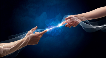 Two male arms reaching for each other, with a smoking electric current connecting their fingers in empty space background concept Stockfoto